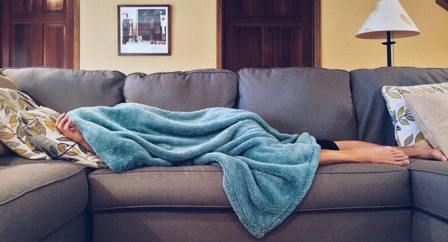 Kvinde ligger på sofa med tæppe over hovedet